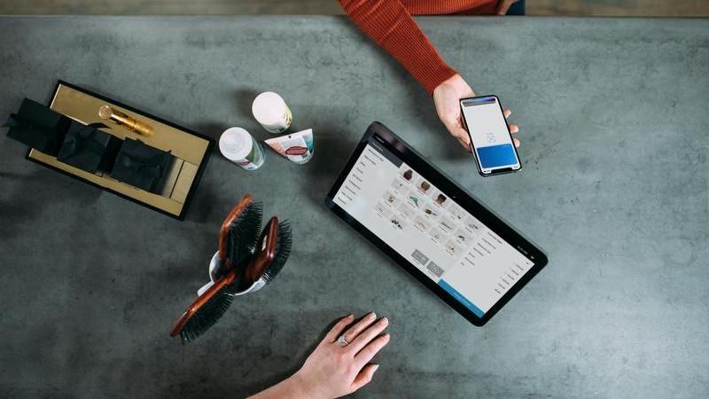 Pessoa no caixa usando o celular para pagamento.