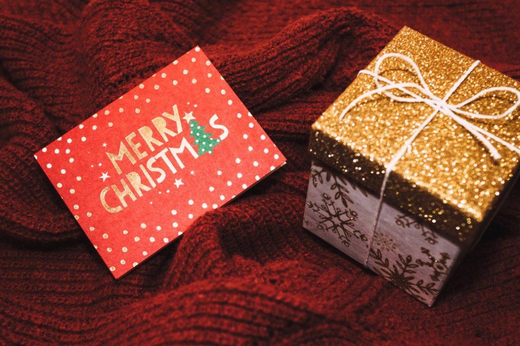 Cartão de natal ao lado de caixa dourada com laço.