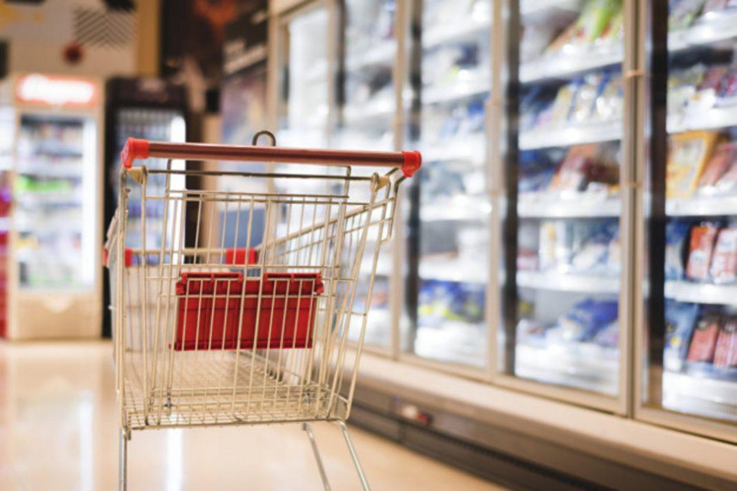 Carrinho de supermercado em destaque ao lado de refrigerador com produtos.