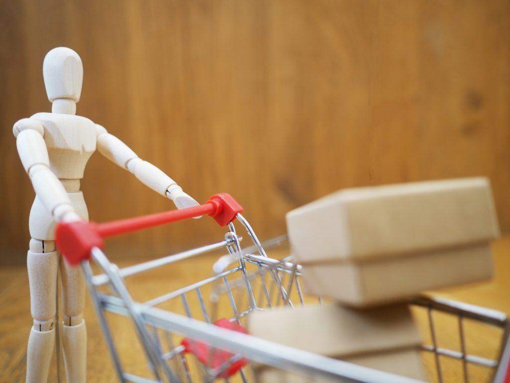 Boneco de madeira empurrando carrinho de supermercado em miniatura