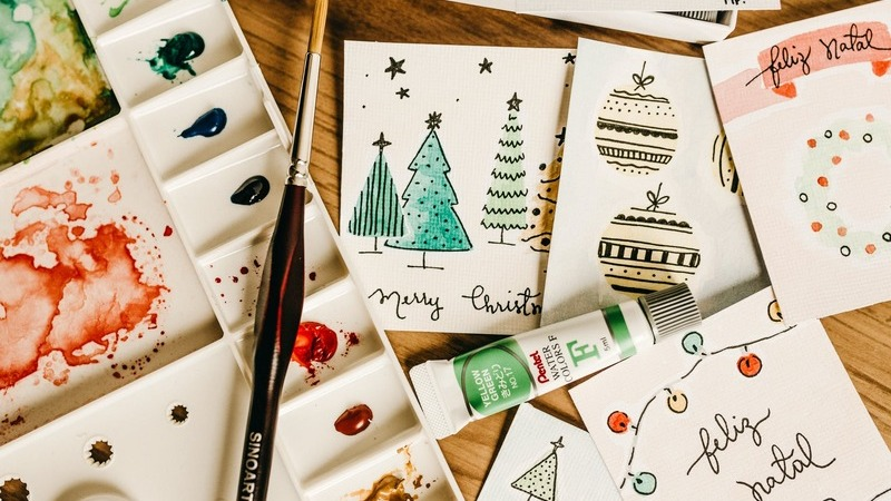 Cartões de Natal e tintas sobre uma mesa.