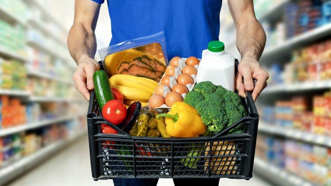 homem segurando cesta de produtos em corredor de supermercado