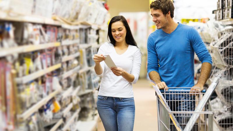 Homem e mulher andando em corredor de distribuidora de materiais de construção e olhando lista de compras.