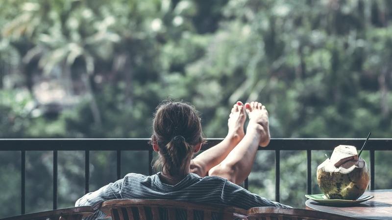 Mulher descansando em uma varanda com os pés levantados e tomando água de coco.