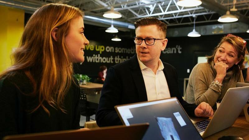 Homem conversando com duas mulheres para fechar negócio