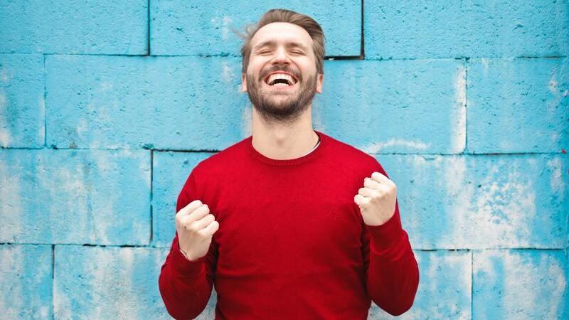 Homem sorrindo e fazendo gesto de vitória com as mãos.