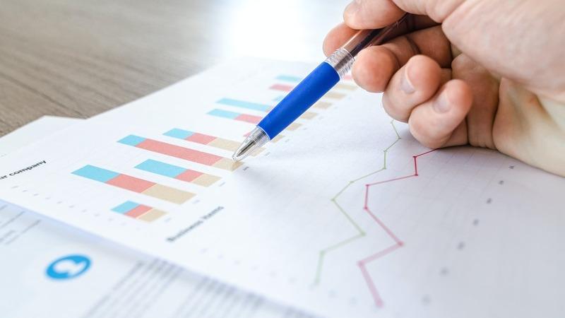 Pessoa segurando caneta sobre folha com gráficos de gestão de compras
