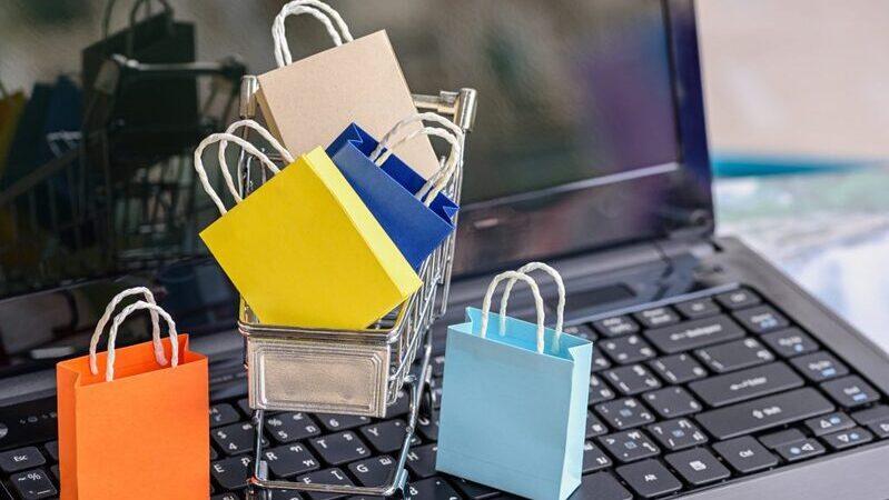 Sacolas e carrinho de compras em miniatura sobre teclado de notebook