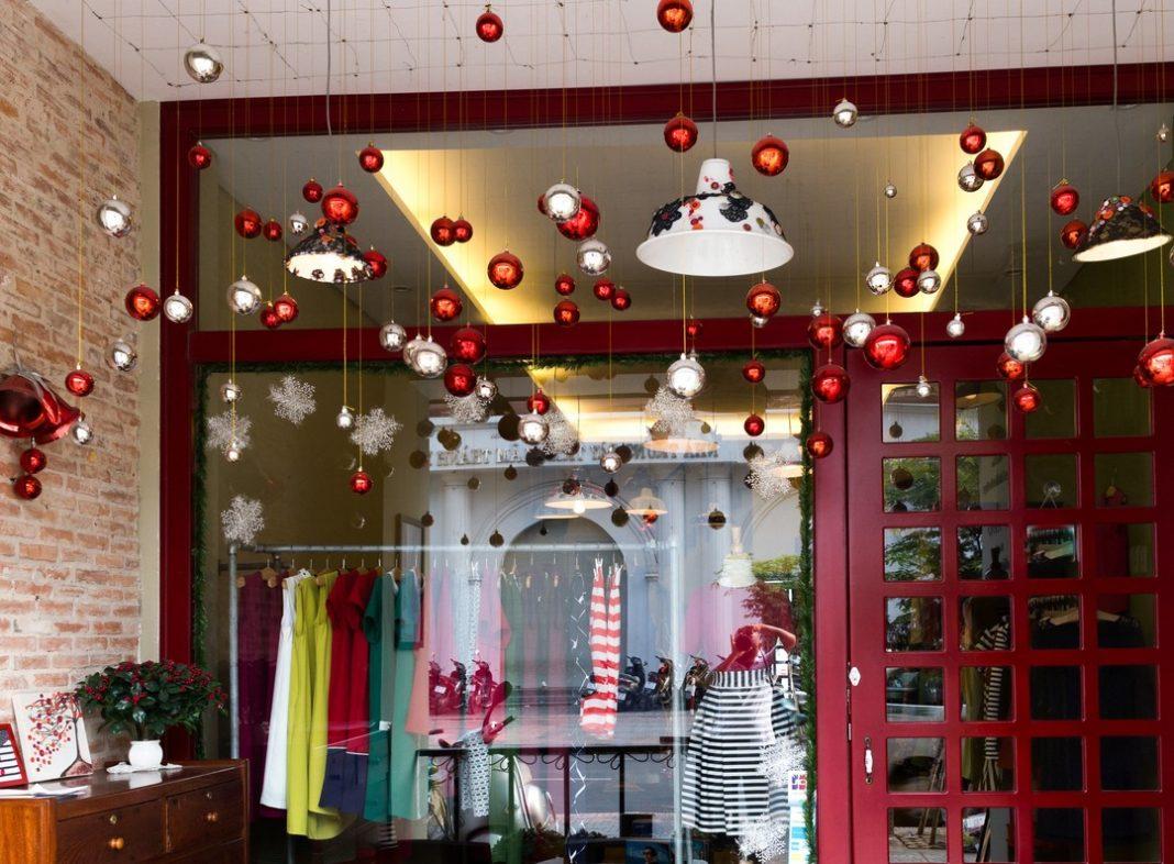 Enfeites natalinos nas cores vermelha e prata pendurados em frente à vitrine de uma loja.