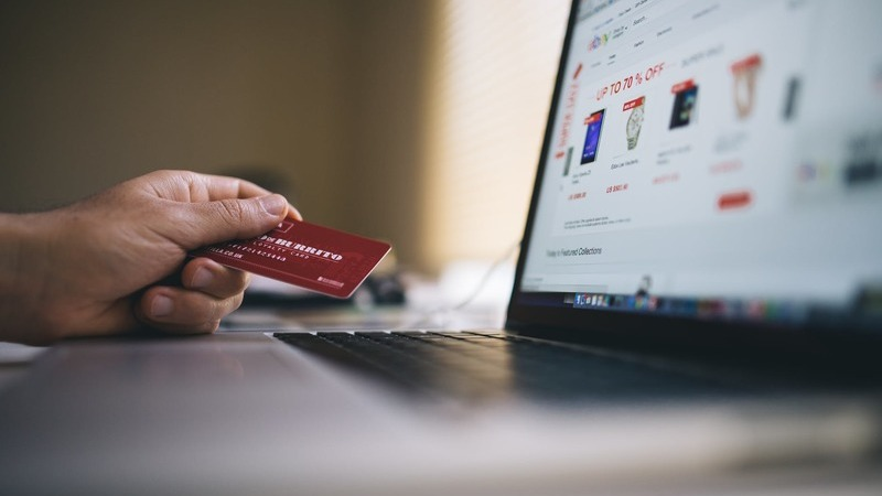 Pessoa em frente a notebook e segurando um cartão de crédito.