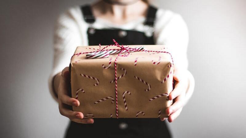 Pessoa segurando pacote de presente com os braços estendidos, como se o oferecesse a quem está do outro lado da tela.