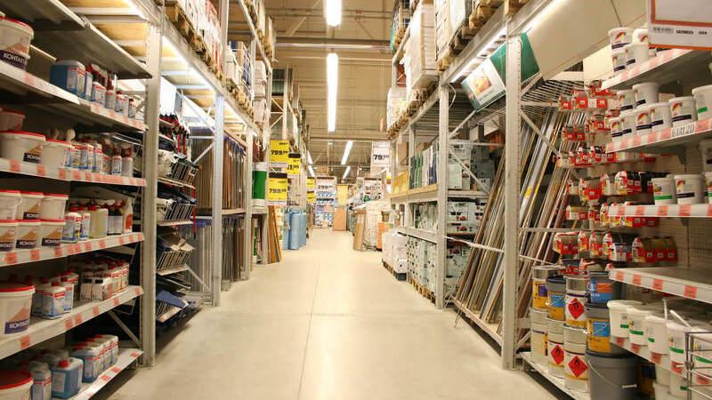 Corredor de distribuidora de materiais de construção com prateleiras de produtos dos lados esquerdo e direito.