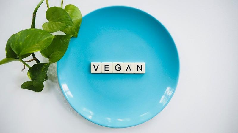 Prato azul com blocos brancos dentro formando a palavra VEGAN