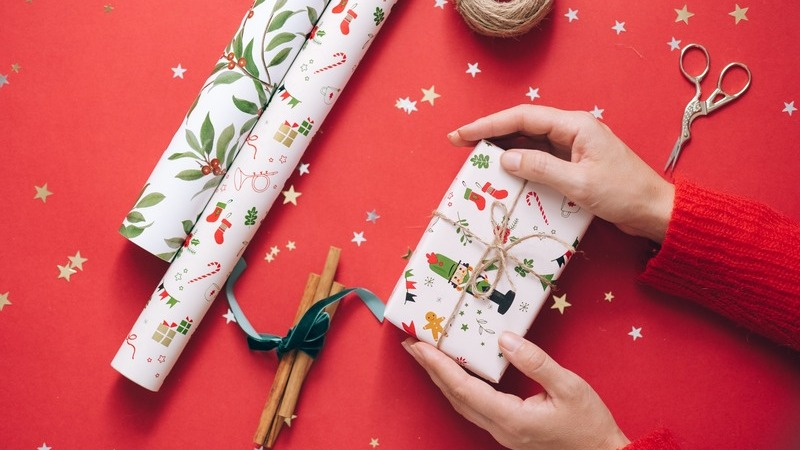 Pessoa embrulhando presente de natal. Ao redor, tesoura e rolos de papel de presente.