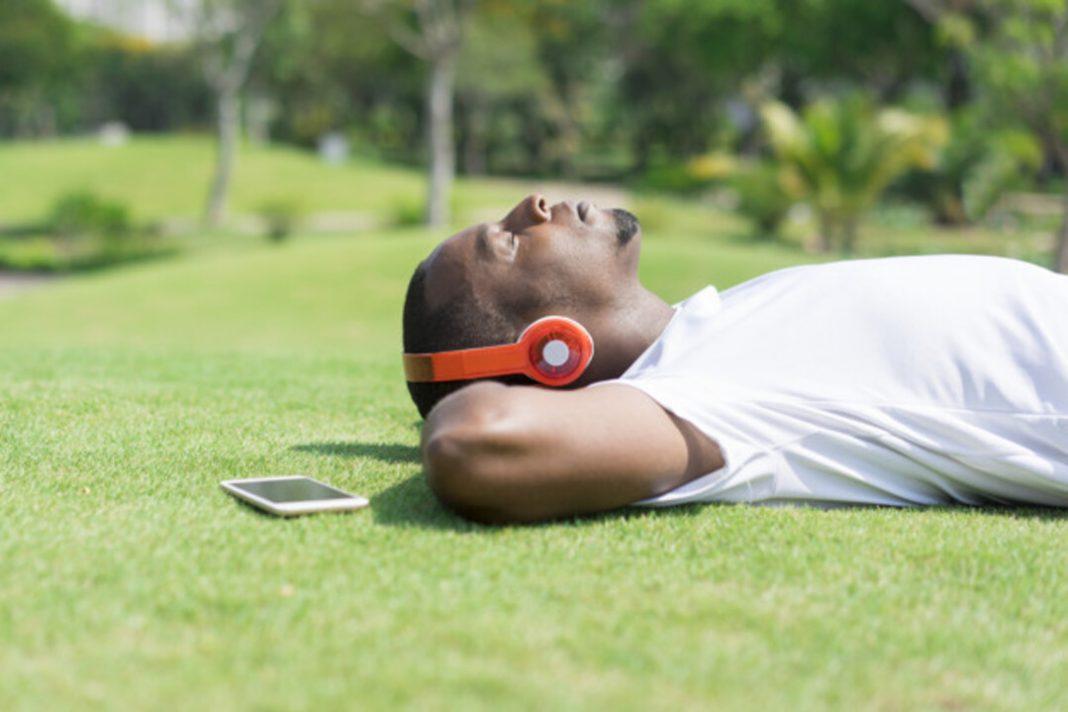 Homem descansando deitado na grama enquanto ouve música com headphones.