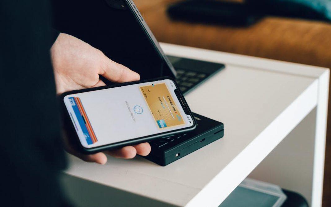 Pessoa segurando celular próximo a leitor de cartão