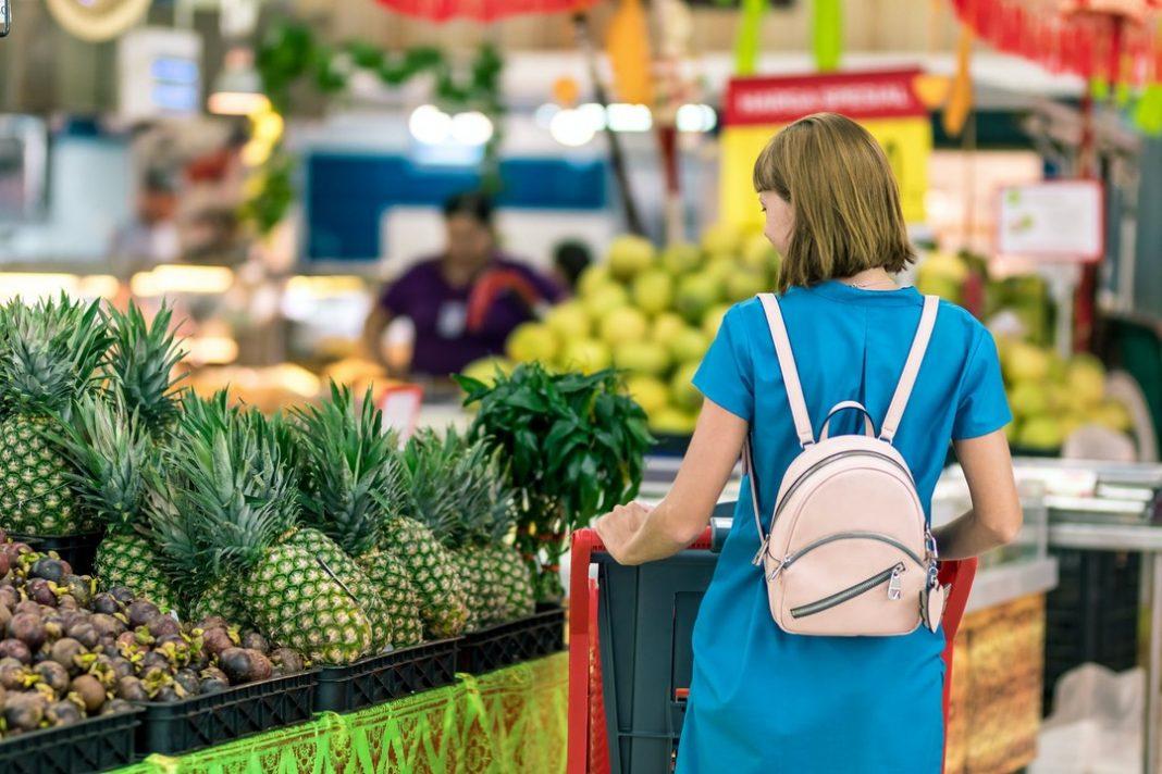 mulher empurrando carrinho de supermercado no setor de frutas e verduras.