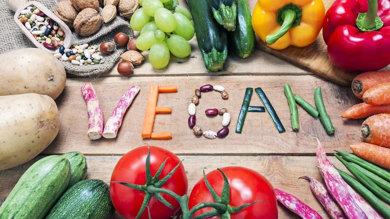 Legumes dispostos em formato de círculo com a palavra VEGAN escrita no centro com pedaços de vegetais.