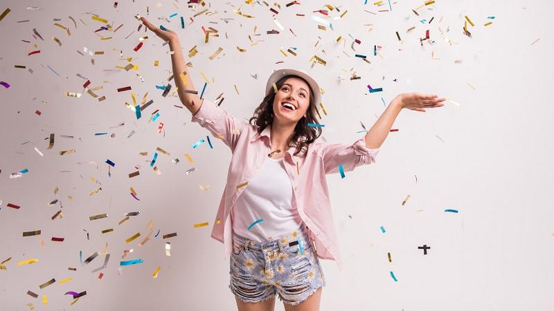 mulher sorrindo com confetes de carnaval