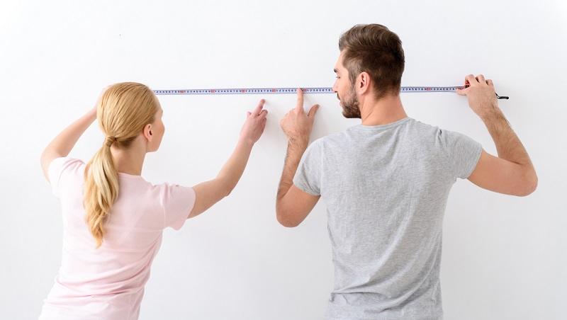 casal medido parede usando fita métrica