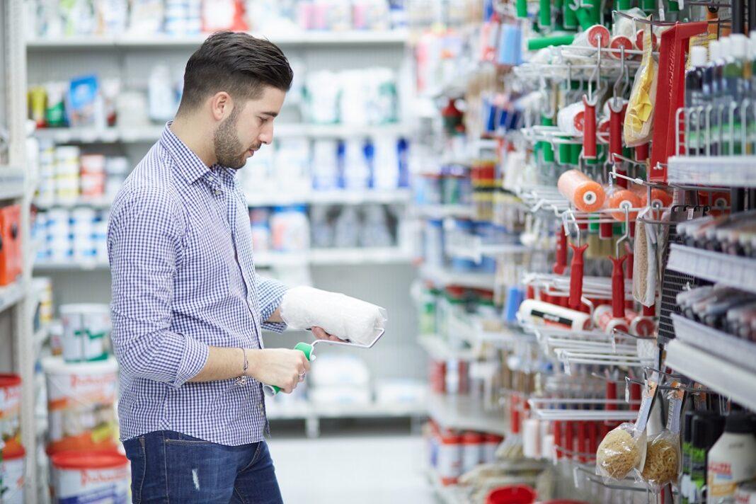 Homem com rolo de tinta na mão em loja