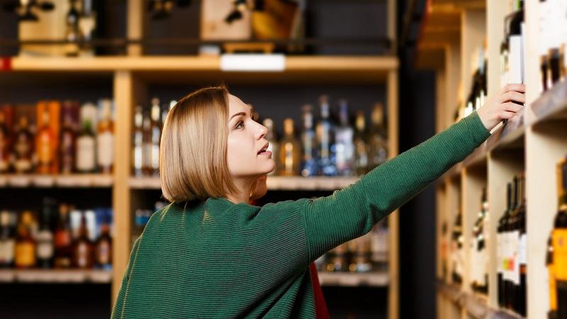 mulher escolhendo bebida no supermercado