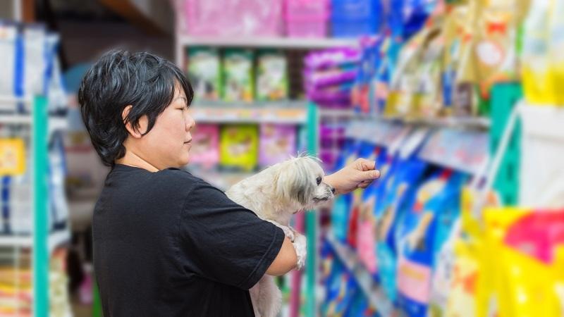 mulher com cachorro comprando ração