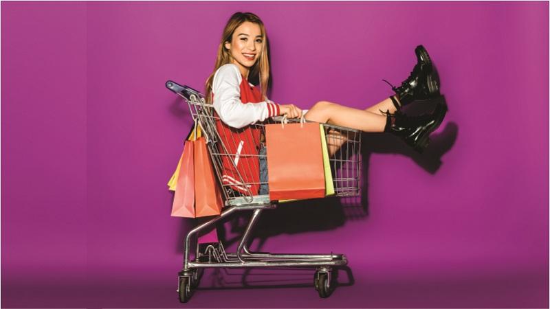 mulher dentro carrinho de compras com sacolas