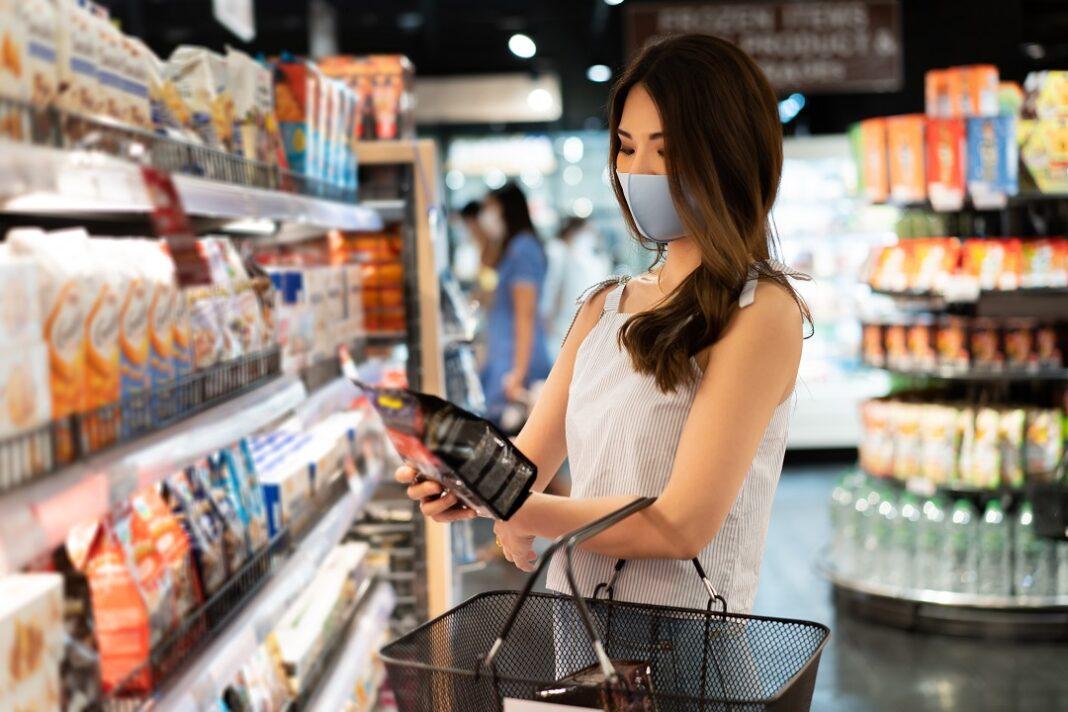 mulher com máscara escolhendo snack no supermercado
