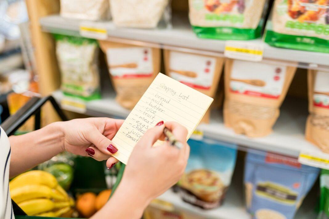 mulher com lista de produtos na mão para comprar no supermercado