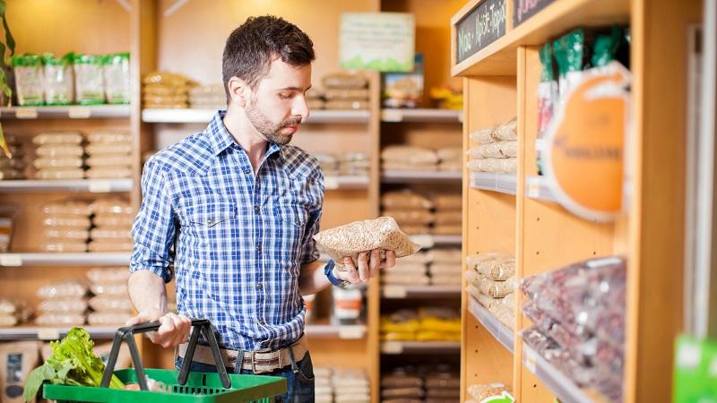 homem com cesta de supermercado na mão lendo sobre produto