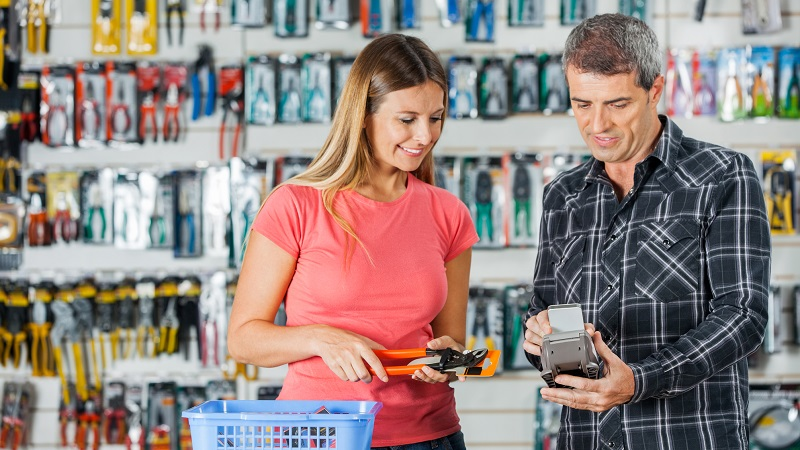 Homem pagando compras através de smartphone na loja de construção