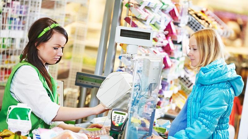 mulher passando as compras em supermercado