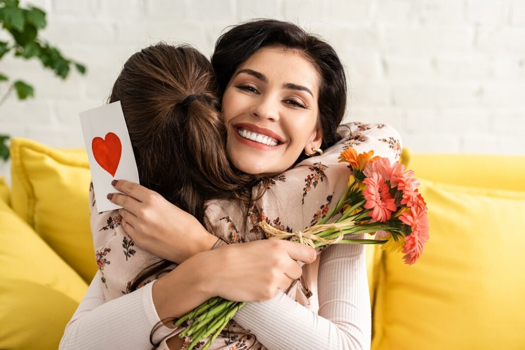 filha abraçando a mãe com flores na mão