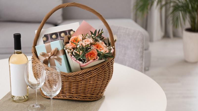 cesta de presente com vinho chocolate flores e taças