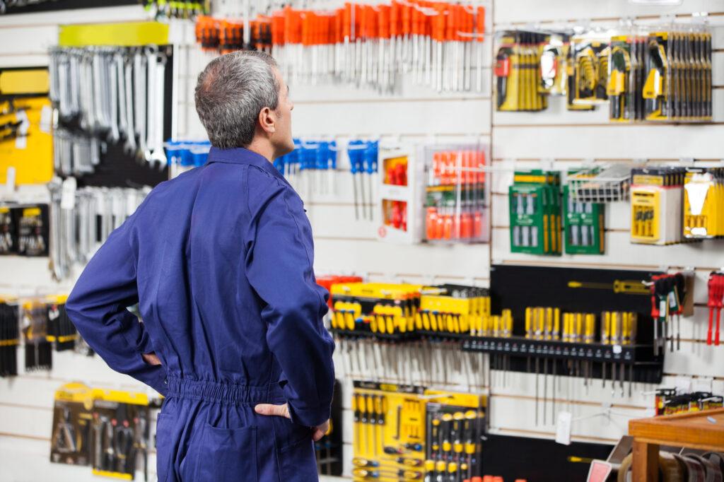 Homem com as mãos no quadril na loja de ferragens