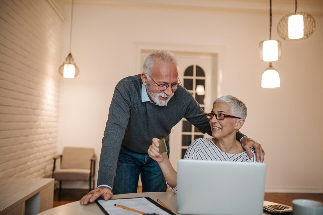 casal de idosos fazendo compras online em casa