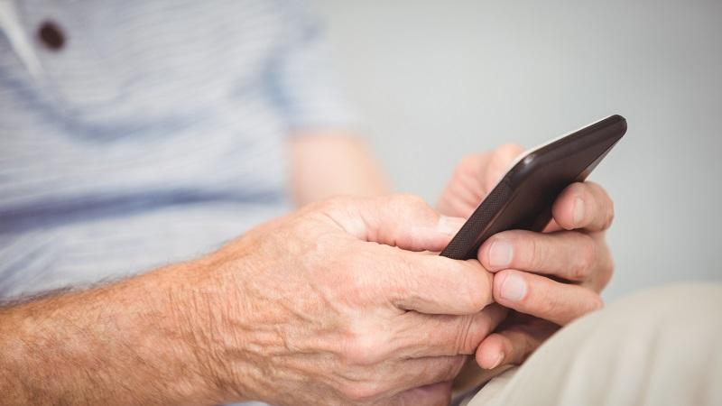 mãos de idosos usando um smartphone