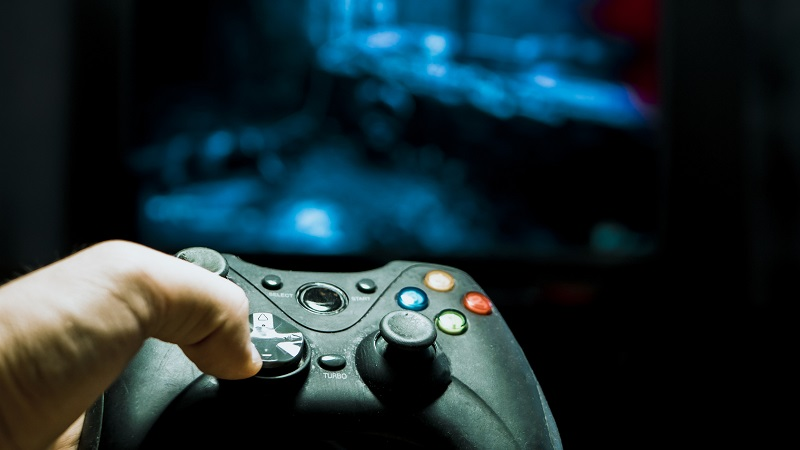 Controle de videogame na mesa e televisão ligada