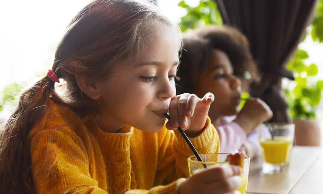 duas crianças tomando suco usando canudinho