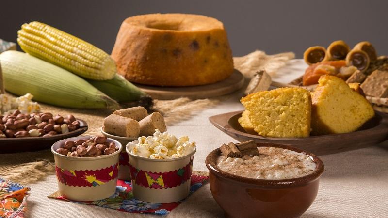 mesa com pipoca bolo milho e comidas típicas de festa junina