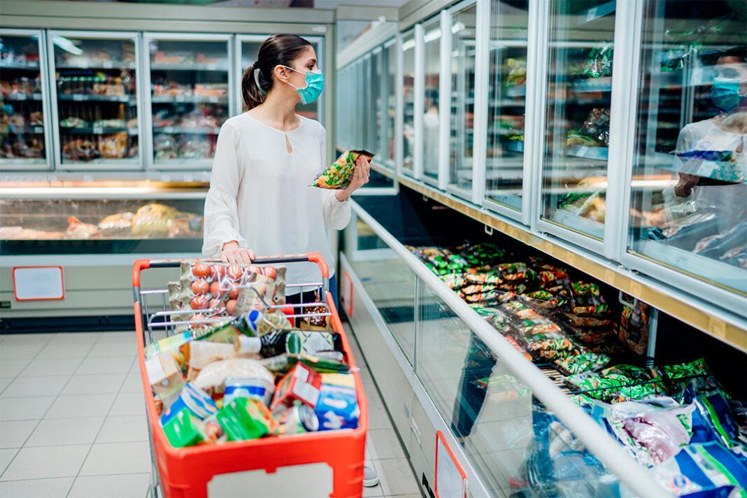 mulher escolhendo alimentos congelados no supermercado carrinho cheio de compras