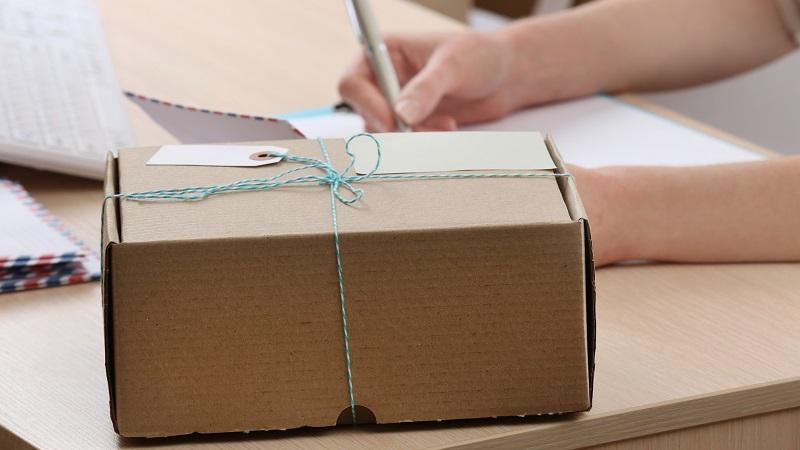 caixa com etiqueta de entrega amarrada a uma fita