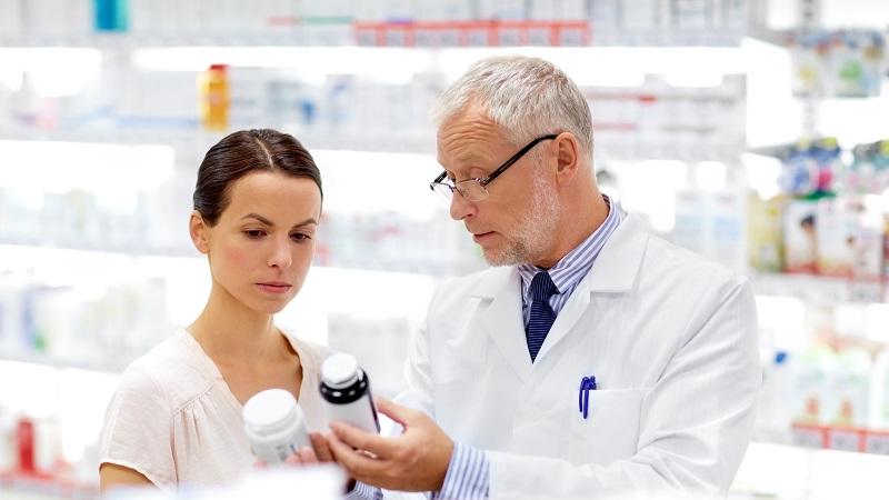 Farmacêutico mostrando remédio para mulher na farmácia