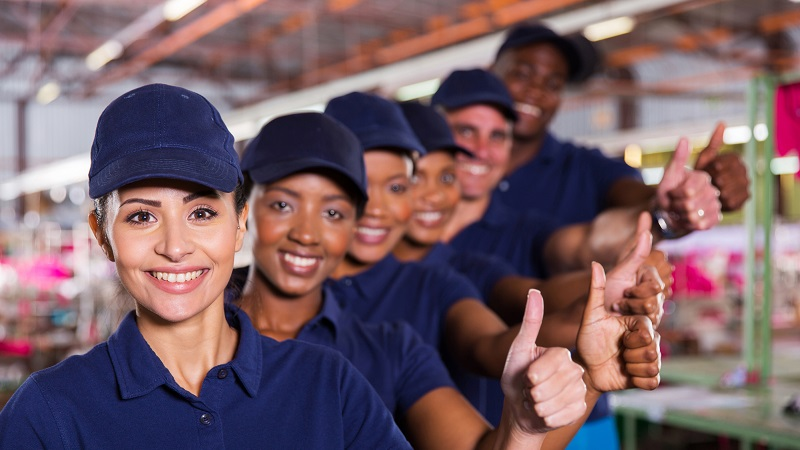 trabalhadores sorrindo mostrando polegares para cima