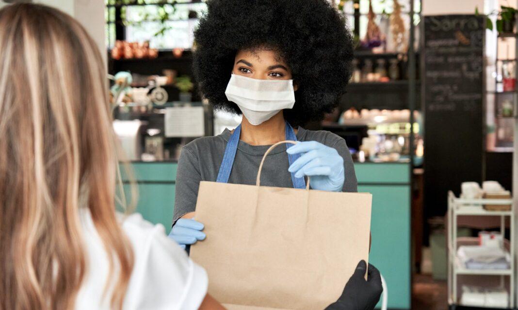 Mulher com máscara fazendo entrega a cliente