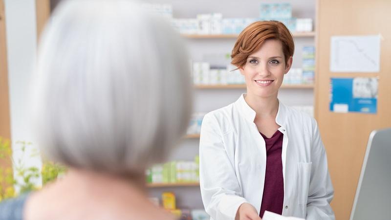 Farmacêutica e idosa conversando na farmácia