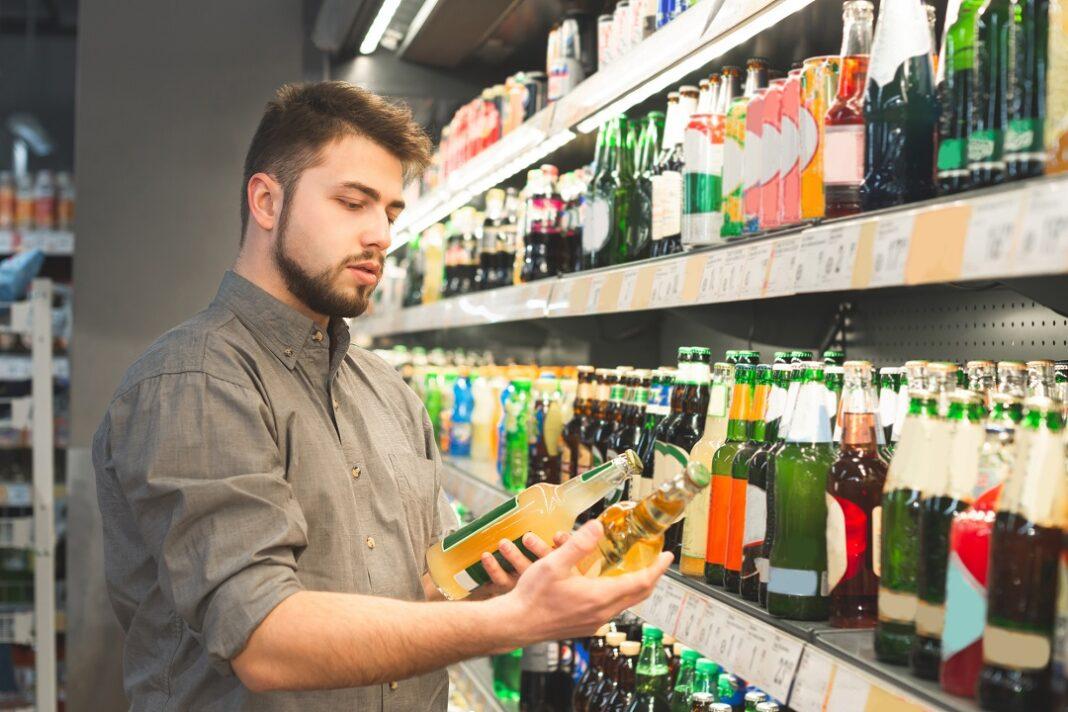 homem com barba escolhendo cerveja em supermercado