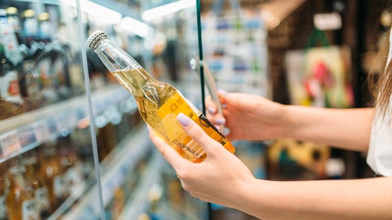 mulher escolhendo cerveja no supermercado