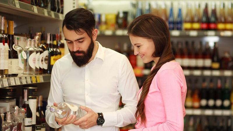 casal escolhendo bebida alcoólica em supermercado